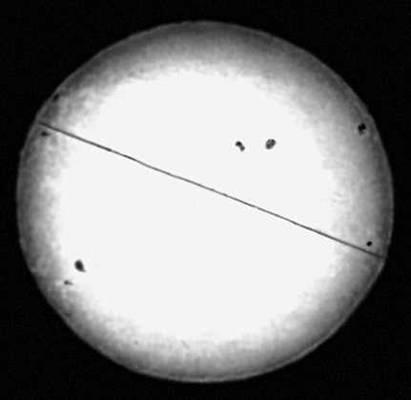 Рис. 1. Фотография Солнца в белом свете. Чёрная линия указывает направление суточного движения Солнца. Видны тёмные солнечные пятна и яркие факелы. Солнце.